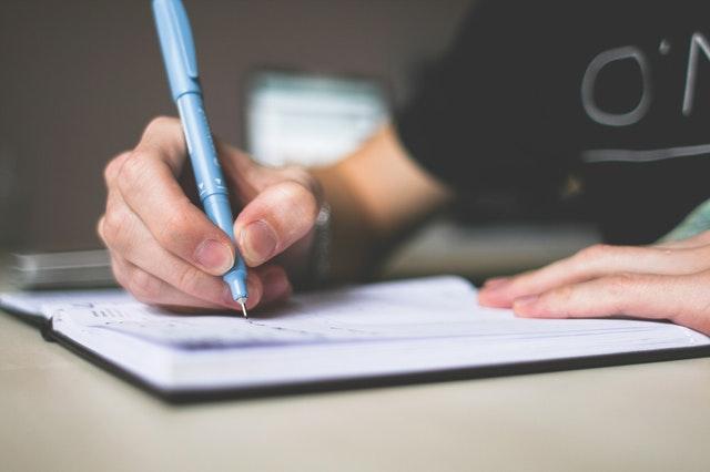 Muž píše modrým perom na papier.jpg