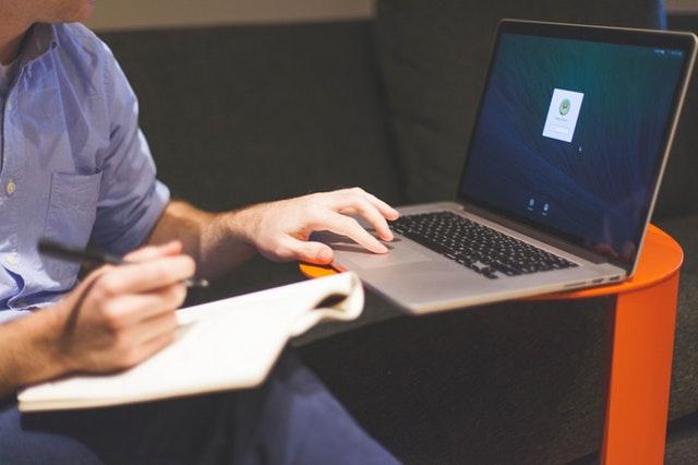 Muž v sivej košeli píše na notebooku.jpg