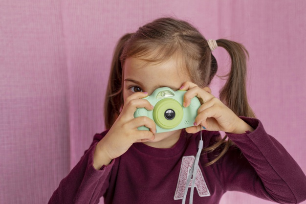 portrait-little-girl-playing-with-camera_23-2148886436